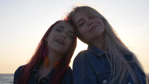 girlfriends smiling in the background of the sunset the wind sways their hair Live Action