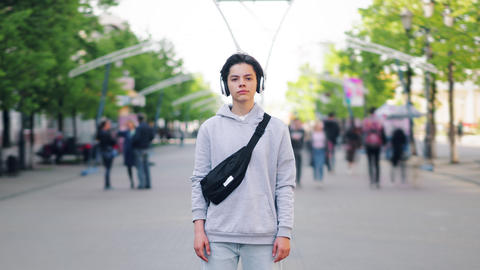 Time-lapse portrait of teenager in headphones standing outdoors in the street Footage