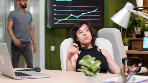 Businesswoman sips coffee while thinking at her desk Footage