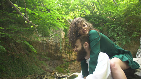 a young woman in a green dress hugs a young man with a beard and kisses him Live Action