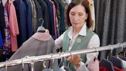 Happy adult woman choosing clothes while shopping in stylish boutique. Cheerful Footage