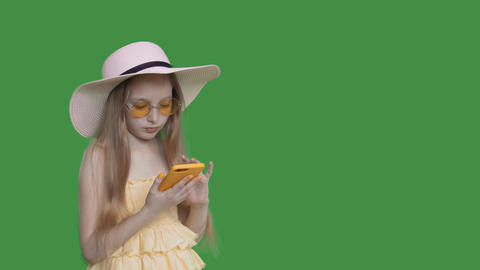 Young girl in yellow dress and sunglasses using mobile phone on transparent Footage