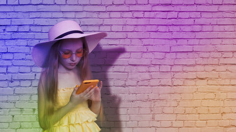 Teenager girl browsing mobile phone on brick wall background in colorful light Footage