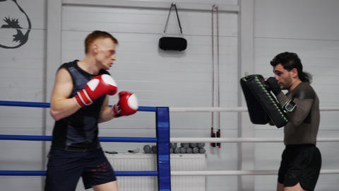 Boxer man training punches by boxing pad while personal training with coach Footage