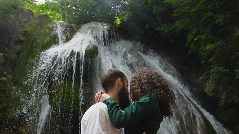 tender embrace of a young couple on the background of a waterfall in the halo of Live Action