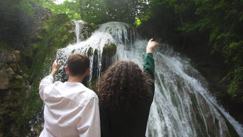 happy couple just married on the backdrop of a stormy waterfall in a mountain Footage