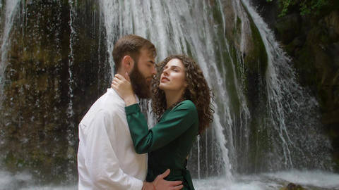 the gentle hugs of a young couple against the backdrop of a waterfall in the Footage