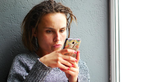 Young caucasian girl enjoys a mobile smartphone on a cafe window Footage