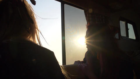 two young women in the sun and glare look through the window of the trailer on a Footage