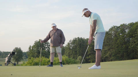 Mature Caucasian man and young middle eastern man playing golf on the golf field Footage