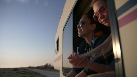 portrait of a pair of young women dressed in jeans in an autotrailer window Footage