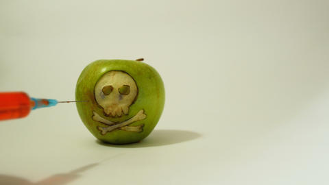 syringe inserted into a green apple with an engraved skull, representative image Footage