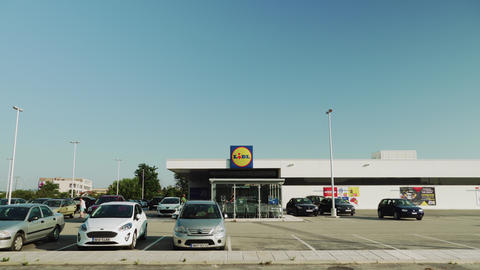 LIDL Stiftung German chain supermarket exterior with company logo and parking lot in Greece Live Action