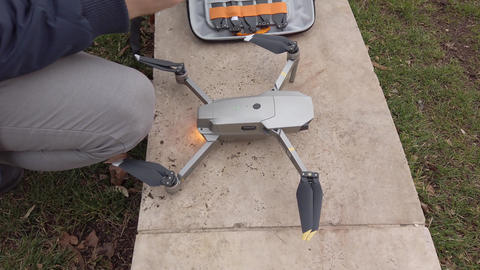 Man preparing quadcopter for take off outdoors Footage
