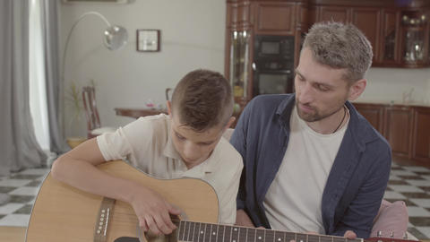 Father teaches son to play guitar at home. Family Leisure Upbringing Footage