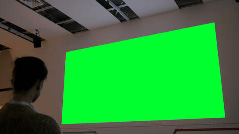 Woman looking at large blank green screen - cinema mock up Stock Video Footage