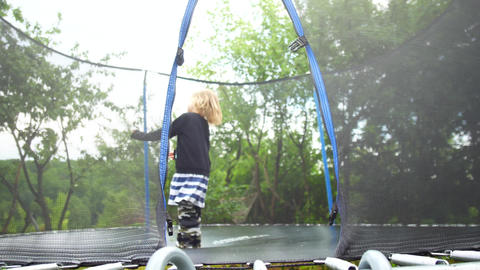Girl jumping on a trampoline that stands in the park among the trees Live Action