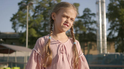 Portrait adorable funny girl with two pigtails playing tennis outdoors Footage