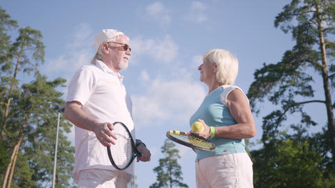 Positive smiling mature couple after playing tennis on the tennis court shaking Footage