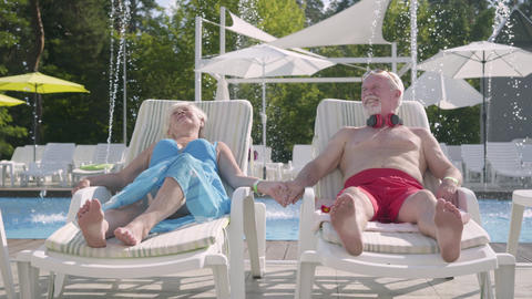 Elderly positive couple lying on sunbeds near the pool holding hands and smiling Footage