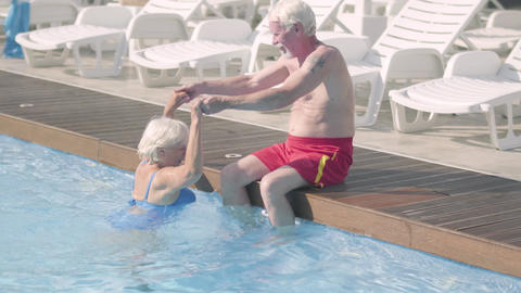 Happy mature couple relaxing at the pool in hotel complex together. The senior Footage