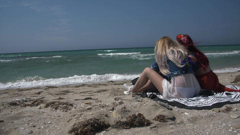 slow motion camera is circling two young sexy women relaxing on a sandy beach Footage