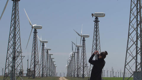 young woman makes a photo of wind turbines on the phone Footage