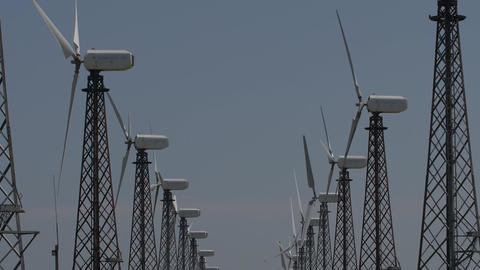 slow motion rows of wind turbines that run against a blue sky Footage