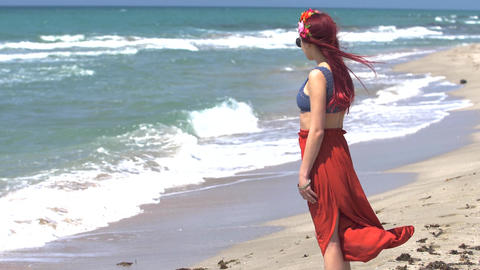 young woman in a red skirt and blue top with red hair flying in the wind looks Footage