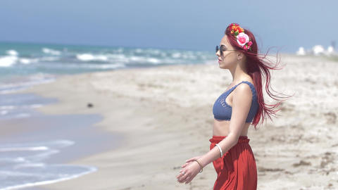 young woman in a red skirt and blue top with red hair flying in the wind and a Footage
