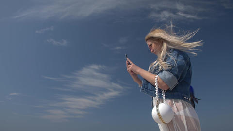 young blond woman with a smartphone in hand against blue sky Slow motion Bottom Footage