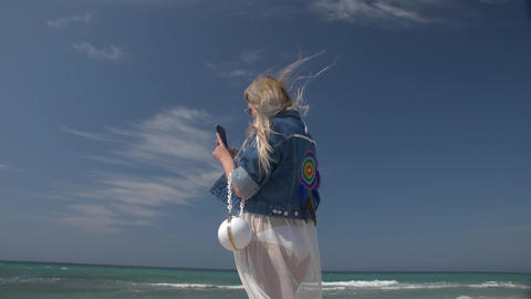young blond woman with a smartphone in hand against the background of the sea Footage