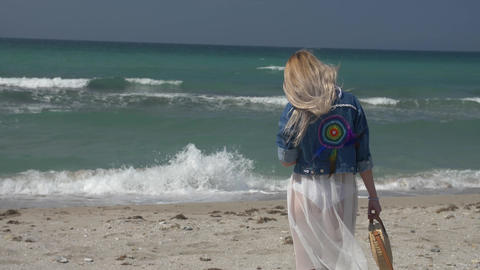young blonde woman in a translucent white dress and denim jacket goes to the sea Footage