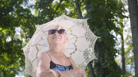 Portrait of positive smiling mature woman in sunglasses standing in the park Footage