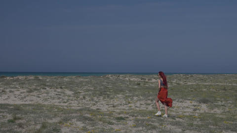 slow motion red-haired young woman in a red skirt walks along the shore towards Footage
