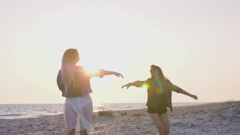 slow motion young women dressed in boho style are having fun on the seashore in Live Action