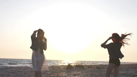 slow motion in the rays of sunset on the beach young women dressed in boho style Footage