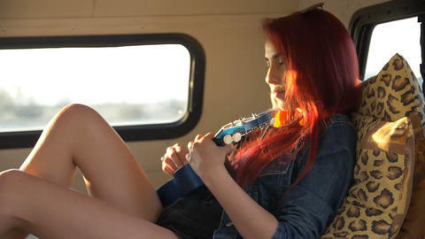 young woman plays the reclining ukulele on the couch in the trailer Footage