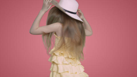 Child girl in yellow dress and hat is dancing ang singing on pink background Footage