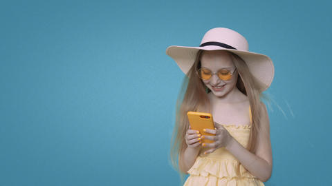 Smiling child girl in yellow clothes is browsing smartphone on blue background Footage