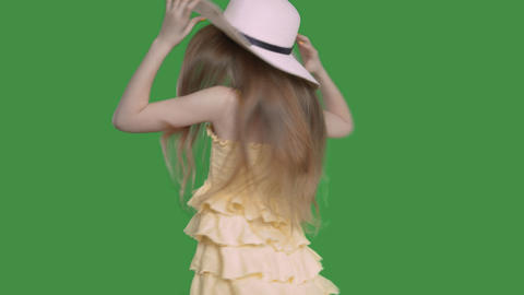 Pre-teen girl in yellow dress and hat is dancing ang singing, alpha channel Footage