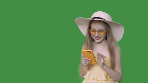Happy pre-teen girl browsing smartphone in summer dress and hat, alpha channel Footage