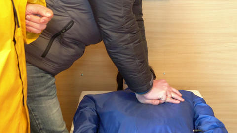Man learns to do compression heart massage on mannequin with instructor help Footage