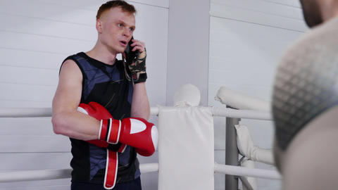 Serious man fighter is talking on smartphone during break of training on Footage