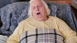 Old woman is sleeping in a recliner Footage