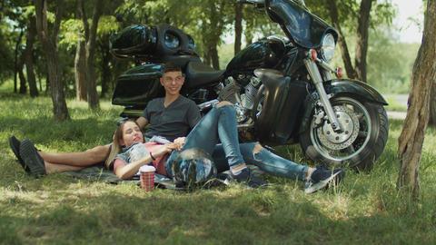 Positive teenage couple relaxing outdoor near bike Footage