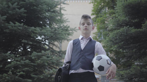 Handsome well-dressed boy standing on the street holding the soccer ball and Footage