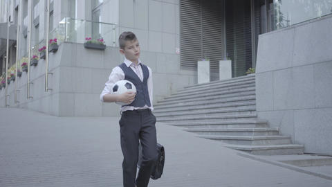 Serious well-dressed boy walking down the street holding the soccer ball and Footage