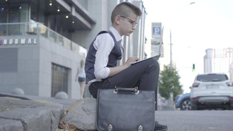 Adorable well-dressed boy in glasses sitting on the street working on the laptop Footage