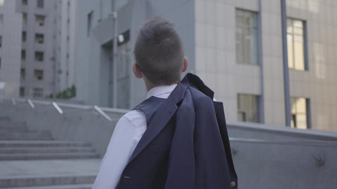 Back view of a handsome well-dressed boy with jacket on his shoulder standing on Footage